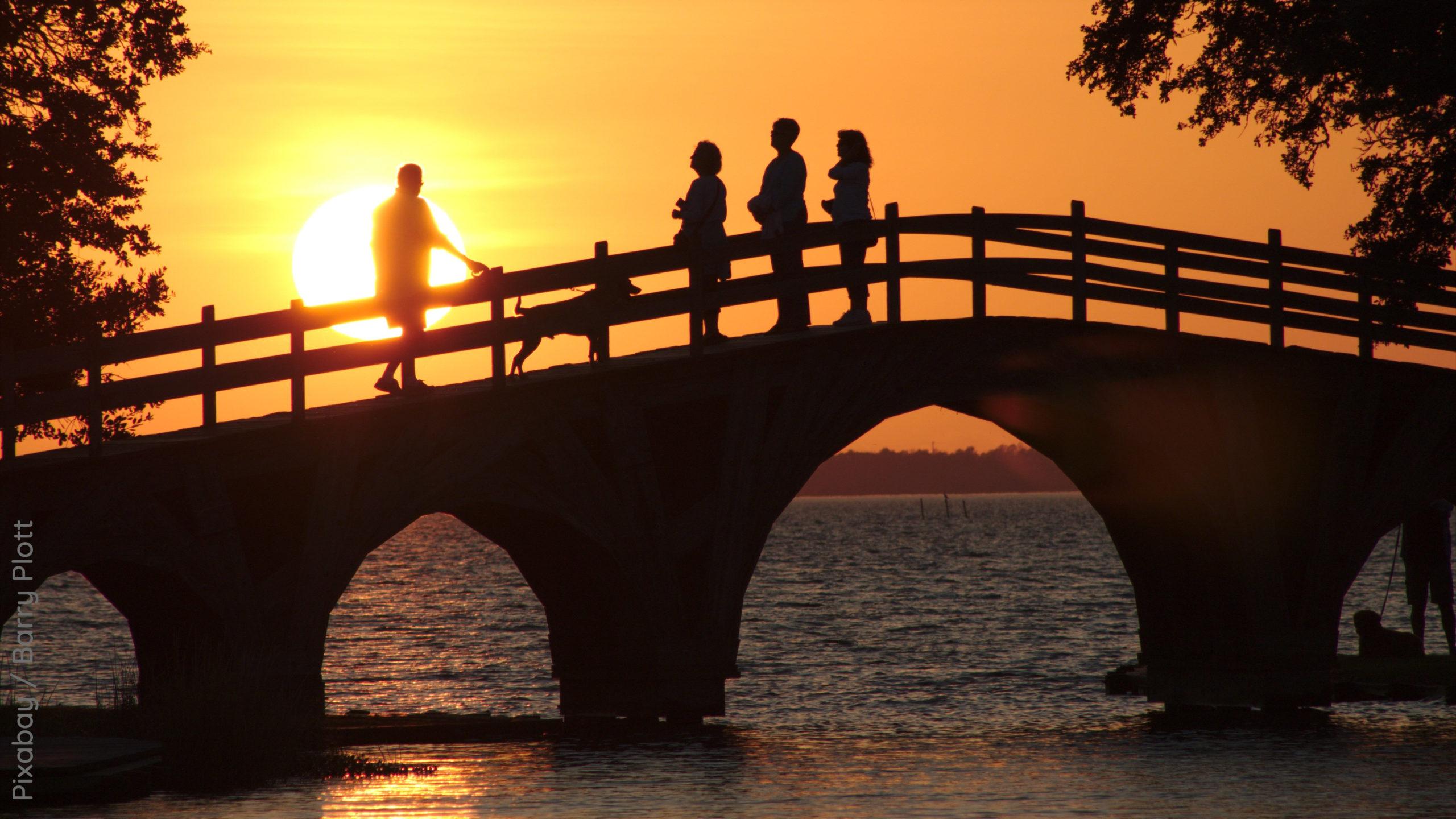 Abendhimmel mit Sonnenuntergang, Menschen auf einer Brücke über das Wasser