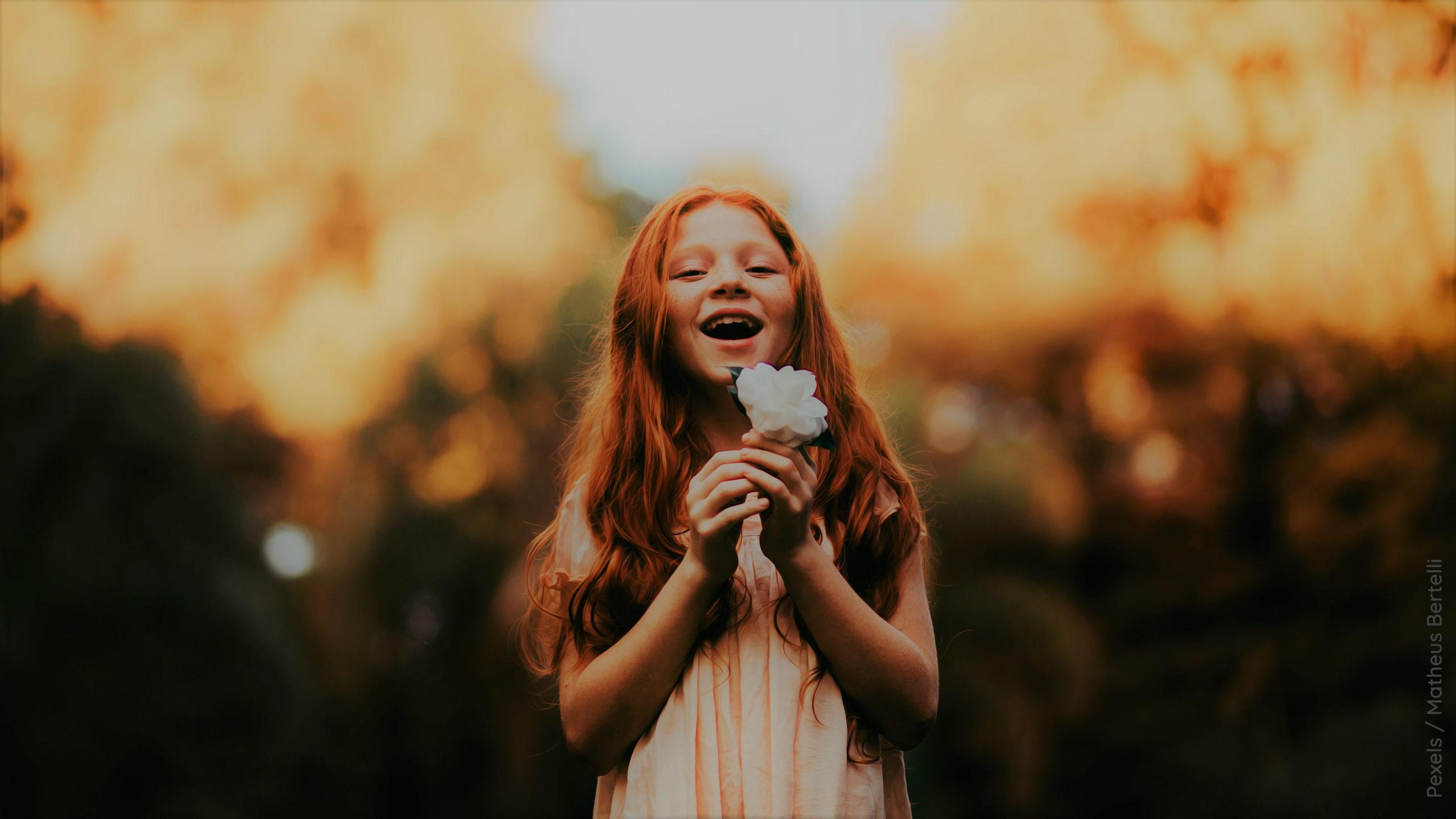 Kind mit einer weissen Blume HIntergrund ist unscharf