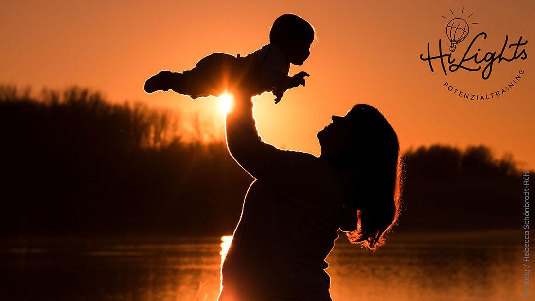Mutter haelt KInd nach oben im Hintergrund Sonnenuntergang - 50
