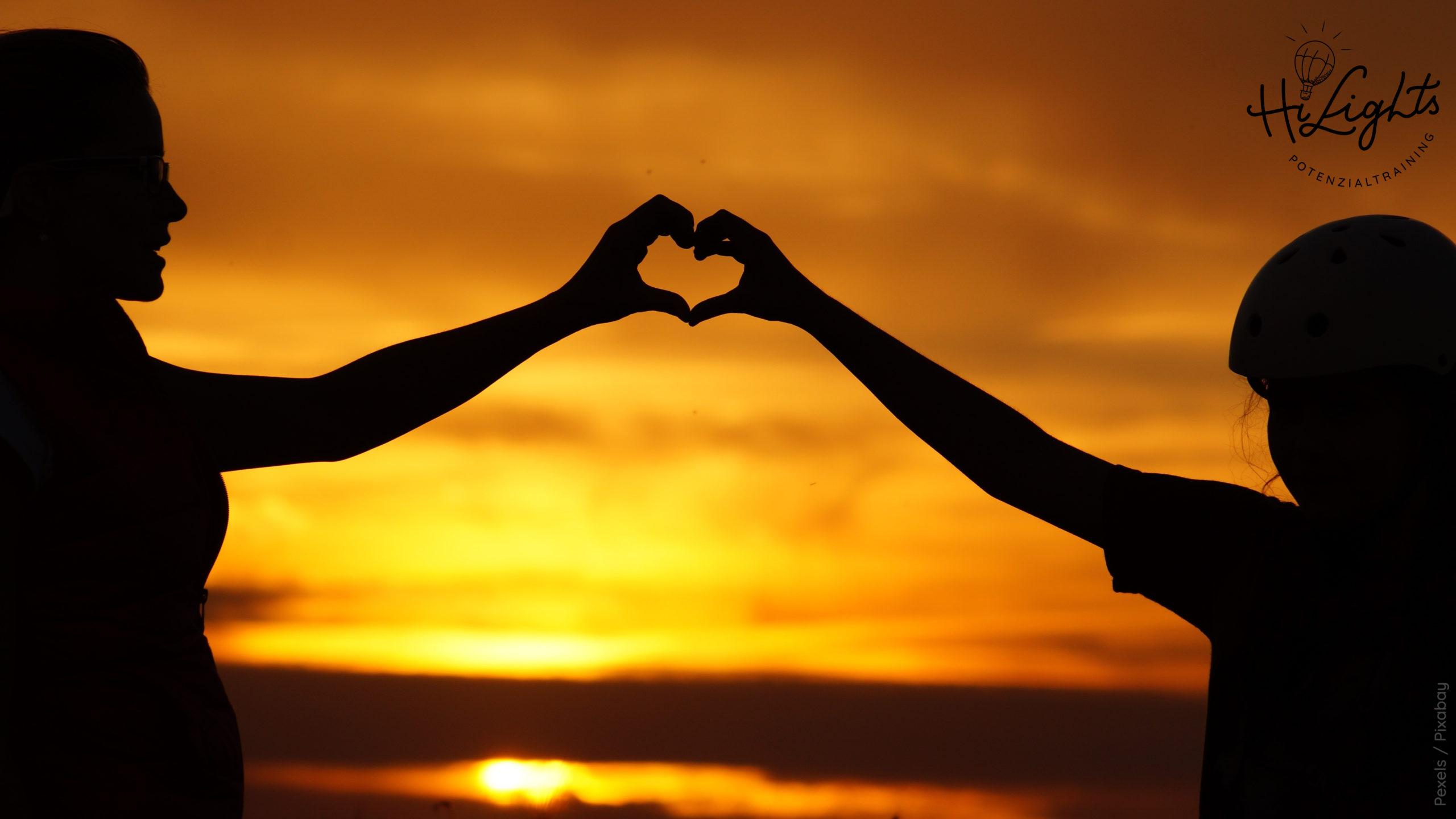 Kind und Frau bilden Herz mit den Händen zusammen silhouette of man